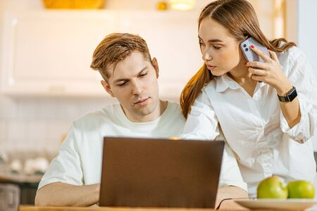 young caucasian married couple solve finance issues online in laptop,couple want to get mortgage, looking for new apartment online. woman talk on phone Foto de archivo