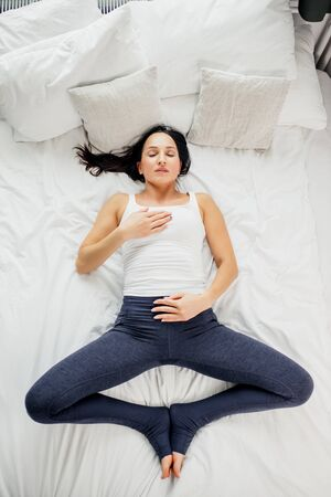 top view on young beautiful woman lying on bed, in shavasana pose,yoga on bed in the morning, beauty and healthy lifestyle concept