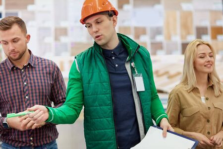 helpful affable warehouse worker help customers with choice, man use document where all instructions and advantages of commodity are writed