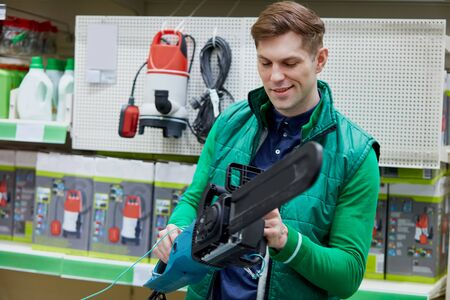 young caucasian salesman in green uniform hold equipment in hands, electric saw at an attractive price in the market, man checks it Banque d'images