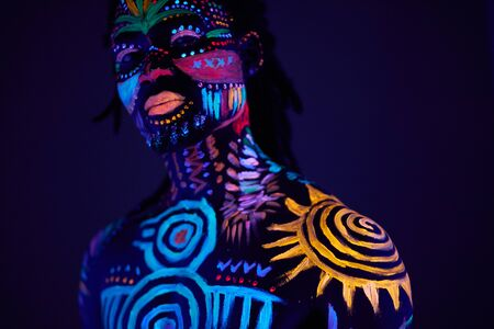 portrait of african man with ethnic pattern, neon makeup in ultraviolet light. fluorescent paints, luminescence prints. body art design of male posing in UV