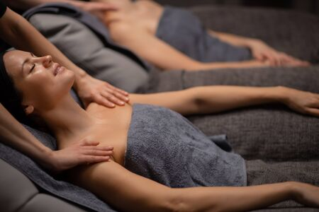 beautiful caucasian healthy women relaxing on massage table, body care in spa salon, massage on face, head, neck, shoulders