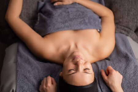 top view on relaxed woman lying on desk after massage, woman wrapped in towel, have rest, enjoy spending time in spa salon