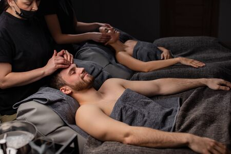 cute young caucasian couple relax at face lift, massage procedure in spa salon. professional cosmetologists carefully do anti aging lifting 写真素材