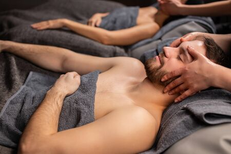 head massage and face lift concept. young caucasian woman lying on massage couch enjoying spa treatment at spa salon. wellness, beauty, health and skin care concept 写真素材
