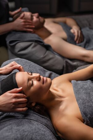 side view on couple getting face and head treatment. relaxed couple lying down on massage bed during facial treatment at asian spa and wellness center