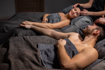young caucasian couple at anti aging face lift procedure, say no to wrinkles and unsmooth skin. professional masseur do massage on head, man and woman relax lying on bed