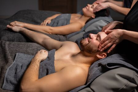 cute young caucasian couple relax at face lift, massage procedure in spa salon. professional cosmetologists carefully do anti aging lifting, couple lie on bed and hold hands together
