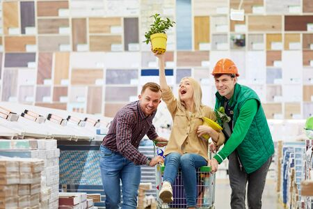enjoy shopping, woman laugh while sitting on trolley, warehouse worker and man roll the trolley, woman hold plants on pots, have fun