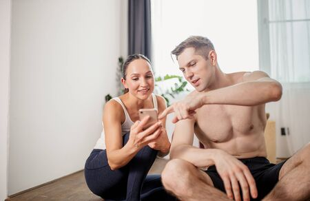 positive young caucasian couple enjoy free time after yoga exercises at home, fitness couple enjoy spending time at home, they do yoga together, use smartphone 写真素材