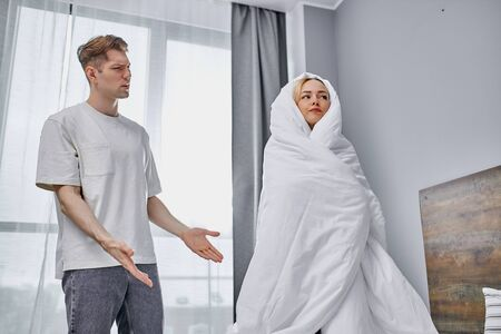 young caucasian man angry at lazy girl wrapped in blanket at home, woman wake up very late, they have quarrel 写真素材