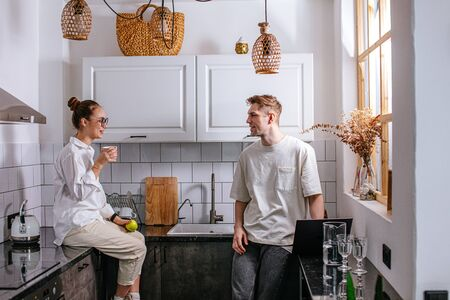 caucasian caring lady supporting working man in the morning. hardworking male work even at home using laptop, woman try to support him and she is always next to him