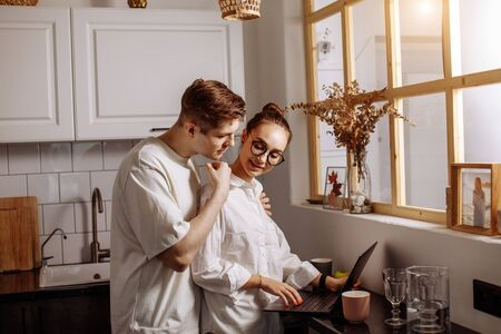 handsome caucasian caring guy support his working wife at home,woman stand using laptop, man hugs her from the back Stock Photo