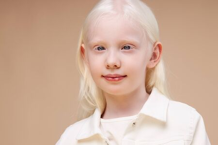 portrait of smiling albino child girl isolated over beige background, unusual interesting appearance of girl is mesmerizing, natural beauty concept Stock Photo