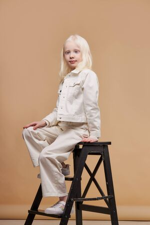 portrait of little fashion model, kid girl with abnormal deviations, unusual appearance, skin abnormality sit on chair posing at camera