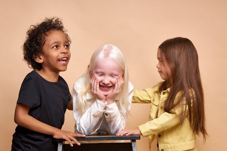 portrait of cheerful positive kids, multiethnic children isolated in studio. adorable afro boy and albino, caucasian girls stand together, posing. international friendship