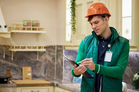 portrait of young caucasian warehouse worker in large warehouse distribution center, shelves with goods in the background, man in uniform Stock Photo