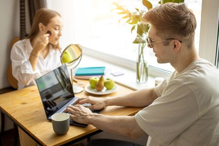 beautiful young caucasian couple spend morning differently, woman do make-up before working day while her husband sit working from home, using laptop. freelance