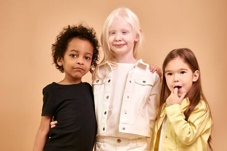 portrait of adorable diverse children isolated. african, albino and european children stand together, close friendship between them. people diversity, children, natural beauty concept Stock Photo