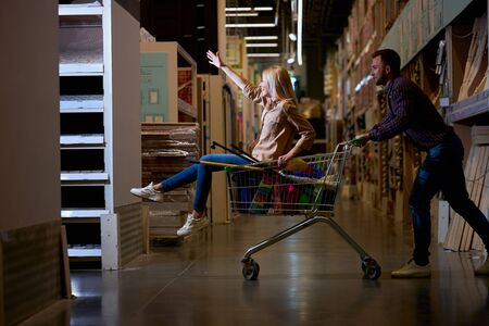 happy caucasian positive couple riding a trolley in big market, girl sit on trolley and enjoy shopping with husband