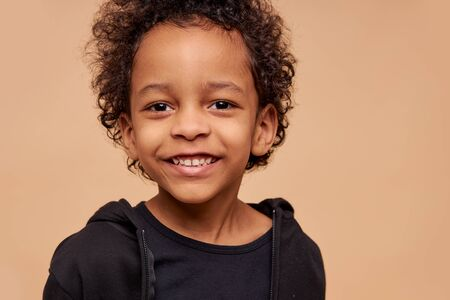 close-up portrait of little dark-skinned boy isolated. positive kid with curly hair look at camera and smile, natural unusual beauty concept