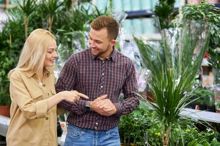 cute good-looking woman show at beautiful plant in market, share opinion with husband, want to make purchase for their new kitchen, in new apartment