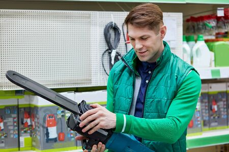 young caucasian salesman in green uniform hold equipment in hands, electric saw at an attractive price in the market, man checks it
