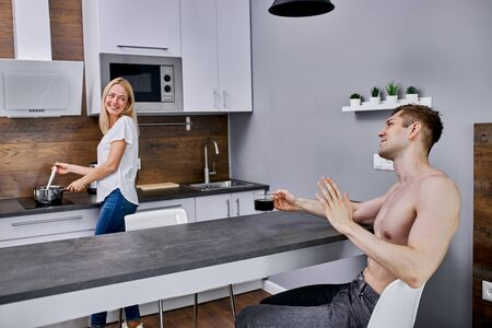 attractive caucasian woman cooking breakfast fir husband, handsome shirtless guy sit making compliments his wife while drinking coffee Stock Photo