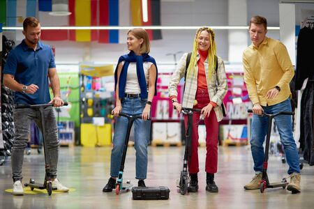 positive caucasian sportive men and women use scooters in aisle of store, try it, going to make purchase, customers have fun, laugh