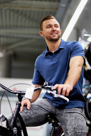 positive smiling man in sportswear store, sit on high-speed sportive bicycle, look side and smile. sport, healthy lifestyle concept Stock Photo