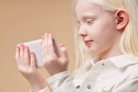 portrait of attractive caucasian albino girl with smartphone, girl with breathtaking beauty use mobile phone. perfect color combination