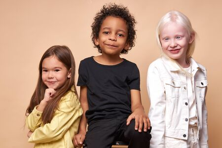 diverse smiling positive children posing at camera, happy black boy and albino, caucasian girls happy together, close international friendship. isolated in studio