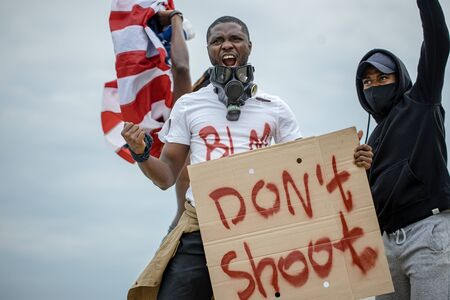 black african american protestors in america with banners, they complain about the police, they hold posters with dont shoot inscription Banque d'images
