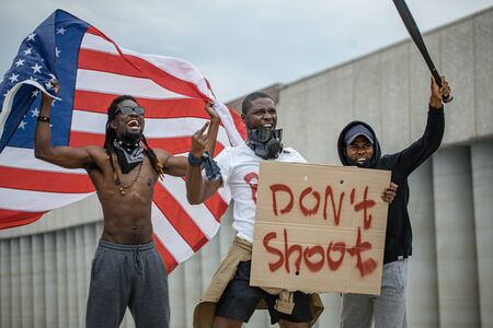 Black lives matter protests go global. three afroamerican people with posters in the street, black people dissatisfied with police injustice and government Banque d'images