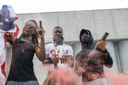 aggressive black people with guns in the streets, young african american people in USA. angry demonstrators dont want to be hurt