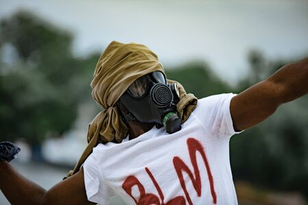 young angry black man in gas mask going to throw a fire bottle, man protests against racism in America