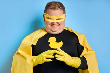 young caucasian cunning fat man conceived somethnig, he is looking at camera, wearing yellow costume and protective gloves. isolated blue background