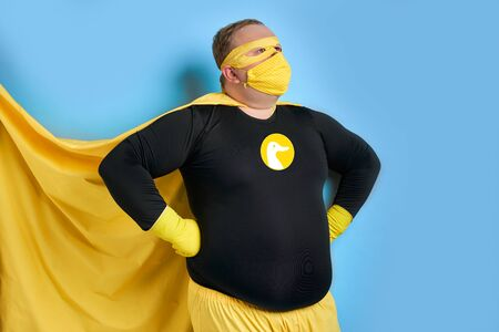 young caucasian fat cleaning man in costume of superhero and in mask, he is ready to save the planet from dirt, man looks side. isolated over blue background 版權商用圖片
