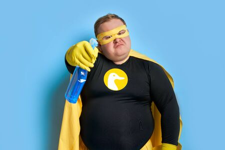 angry caucasian fat man in yellow costume applies detergent at camera, he is tired of dirt. cleaning concept