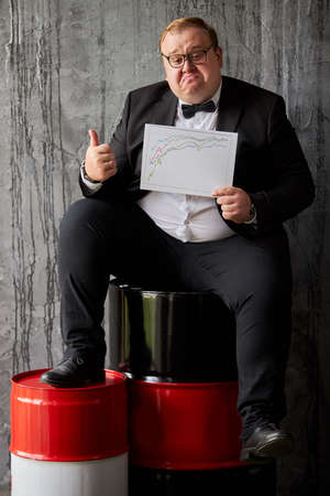 young caucasian businessman has good news, he is happy with oil industry nowadays, sits on oil barrels and look at camera