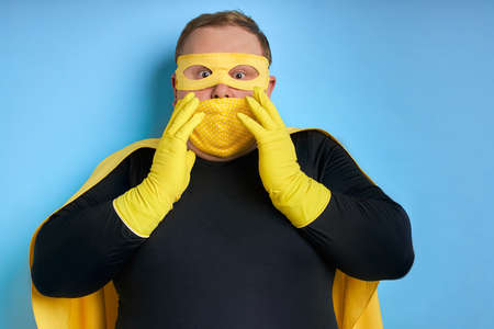 suprised caucasian superhero man in mask isolated over blue background. crazy guy in shock, wearing protective gloves