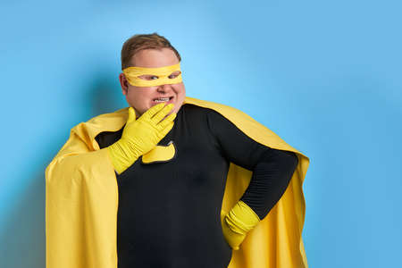 suprised fat superhero man closing his mouth isolated over blue background. young guy in mask, wearing protective yellow gloves looks at camera