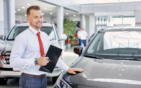 portrait of smiling car dealer at work, man in white formal shirt ready to talk about cars, automobiles and their chaacteristics to customers