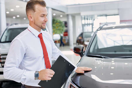 young confident caucasian salesman discuss auto with buyers, friendly man likes his job in dealership