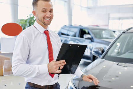 portrait of positive smiling caucasian man consultant in dealership, man during his work, talking with clients. man holds paper documents and look at camera