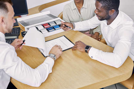 black clients sign a contract while sitting at table with salesman, professional worker of dealership explain terms of the contract and show where to sign Standard-Bild