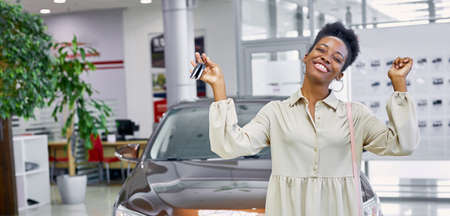 portrait of young and beautiful black woman with keys from her new car, she is happy in dealership, luxurious car in the background