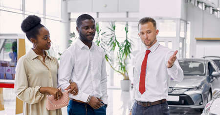 affable caucasian car dealer consult customers, give necessary information about automobiles and show the best car in their car salon