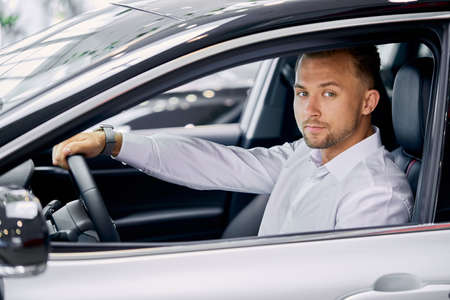 portrait of young handsome caucasian guy sitting behind the wheel of new car, man liked luxurious automobile, want to buy it