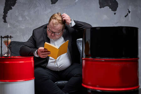 fat caucasian oil businessman thinks how to solve his oil business, he has no time. man reading necessary information, oil barrels next to him. oil industry, crisis concept Reklamní fotografie